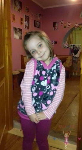 mosolygós kislányon, wellsoft kapucnis mellény, szürke alapon pink pillangó és szív mintával, kép.