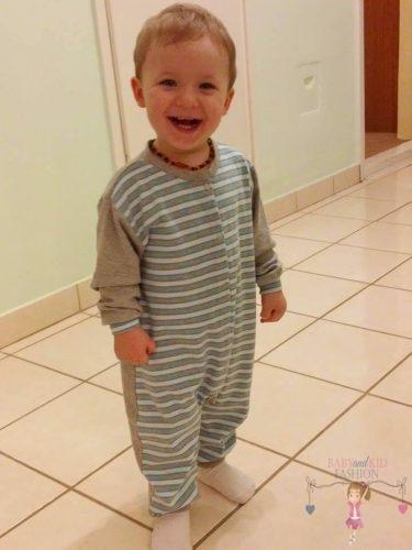 babyandkidfashion kisgyermek, a kisgyermek kezeslábas pizsamában mosolyog, kép.