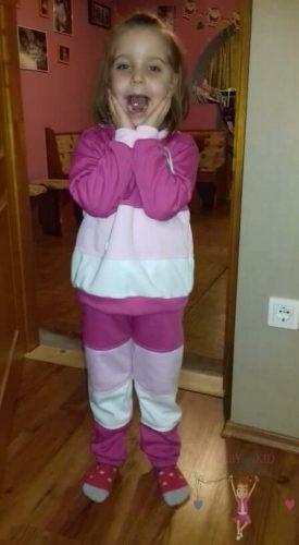 mosolygós cuki kislány, rózsaszín, pink, fehér színek variációjából készült kapucnis szettben, kép.