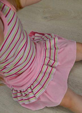 Lány szoknya, puha pamutból. Felsorolom, hogy milyen elvárások vannak felénk, a Magyar kislány szoknyák felé. Rózsaszín lányka szoknya, pink-fehér-kiwi csíkos fodorral, ül a földön, kép.