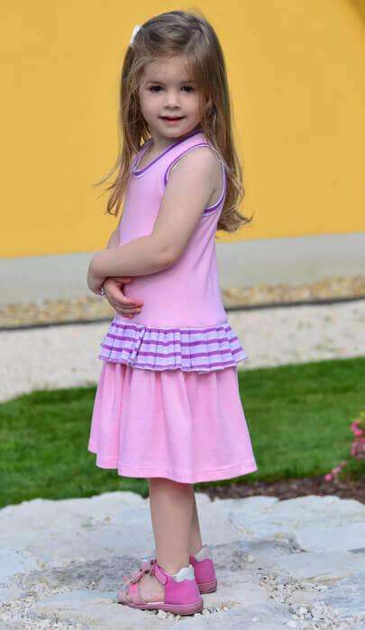 lány ruhák olcsón, rózsaszín fodros ruhában, lila csíkos fodorral álló, mosolygós, hosszú hajú kislány, kép.
