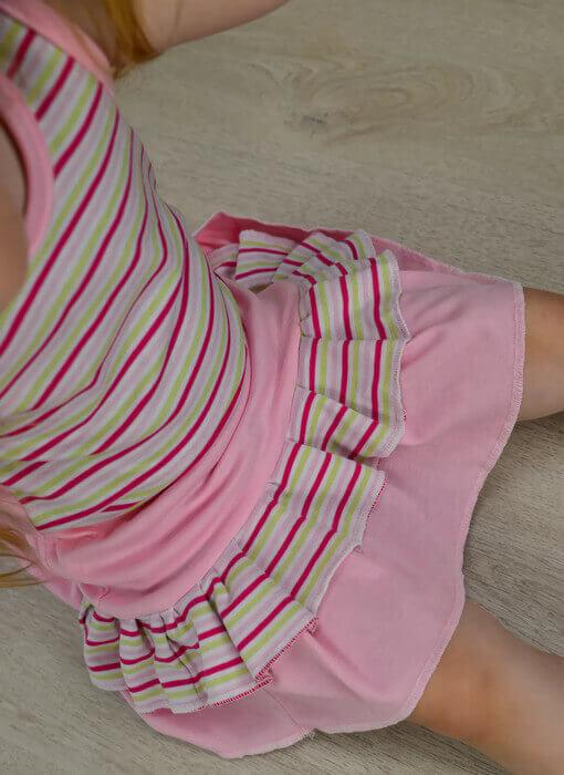 Kislány szoknya szabásminta, szabásminta készítés fortélyai. Rózsaszín színű, pink-rózsaszín csíkos fodorral, fodros, gumis derekú szoknya, kislányon, aki ül, kép.