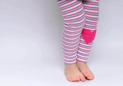 kislány áll pink csíkos leggingsben, pink szívvel, kép.