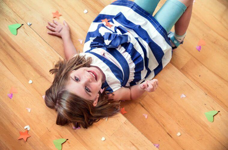 babyandkidfashion, mosolygós kislány, egyedi készítésű kék csíkos ruhában fekszik a képen.