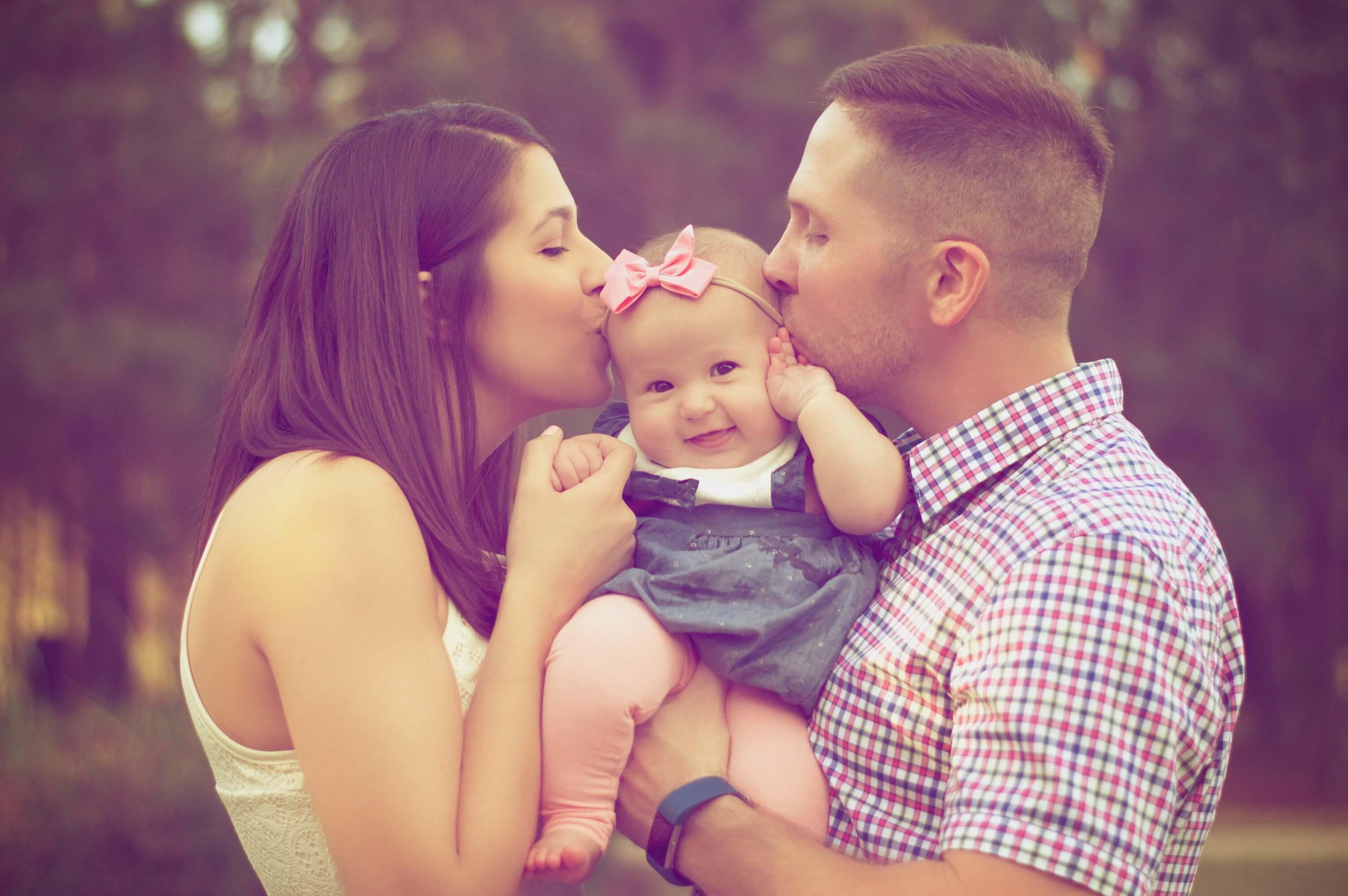 babyandkidfashion, anyuka és apuka boldogan csókolják mosolygós kislányukat, aki magyar babaruhát visel a képen..