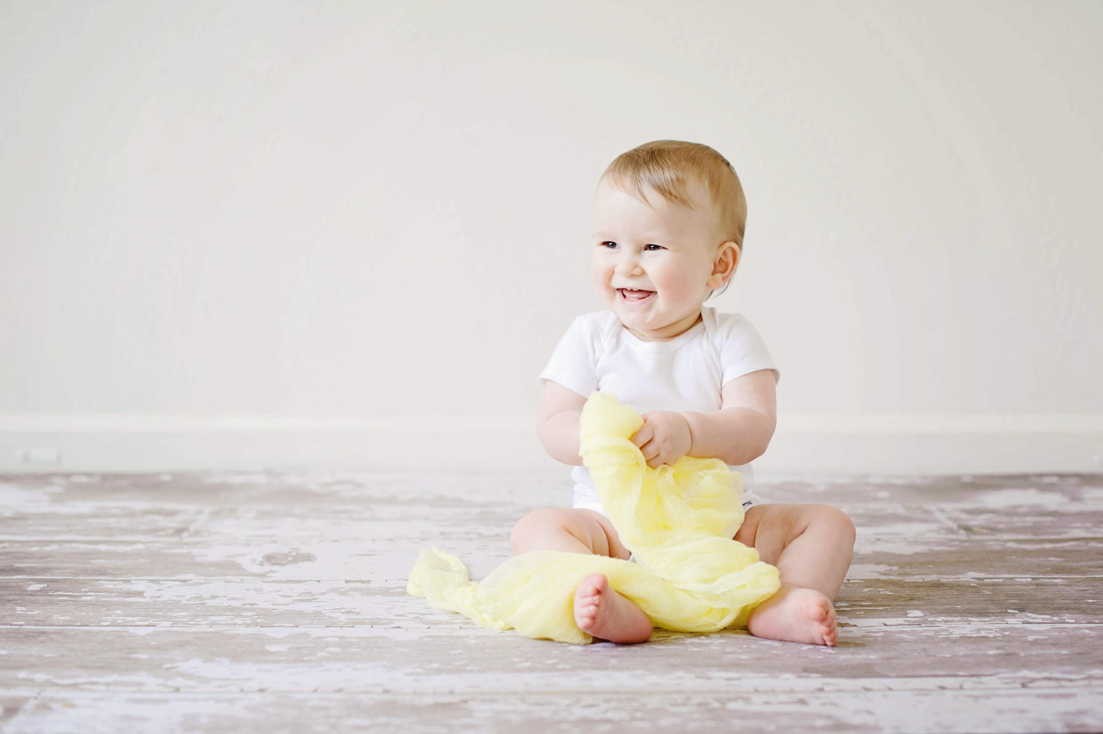 babyandkidfashion babaruhában csücsülő mosolygós kisbaba, aki magyar pamut anyagból készült fehér bodyban mosolyog a képen.