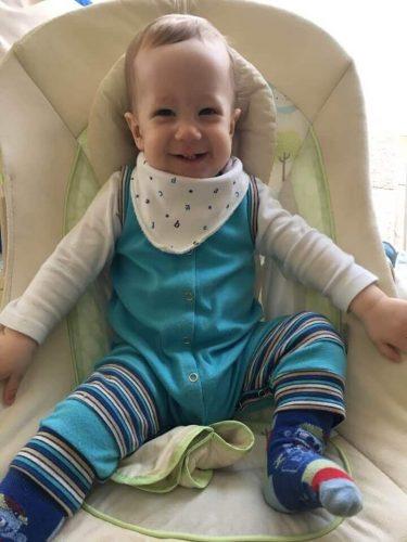praktikus babaruhák, mosolygós kisbaba kék babaruhában, kép.