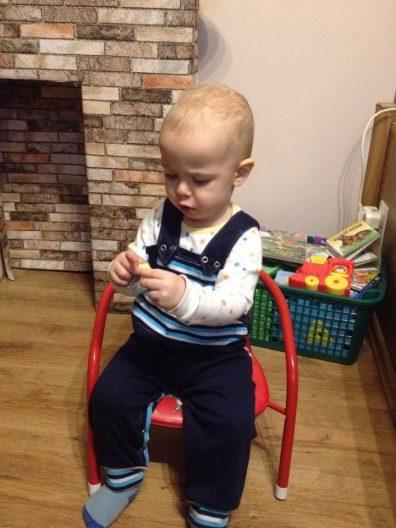 baba kantáros nadrág, kisfiún, ahogy ül egy kisszéken.