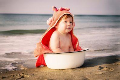 babaruhák mosása, kisbaba ül egy lavorban, mögötte a tenger.