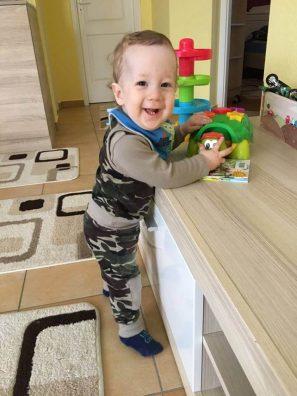 terepmintás babaruha, kisfiús terep mintás szett, egy mosolygós kisfiún, aki játékot tart a kezében, kép.