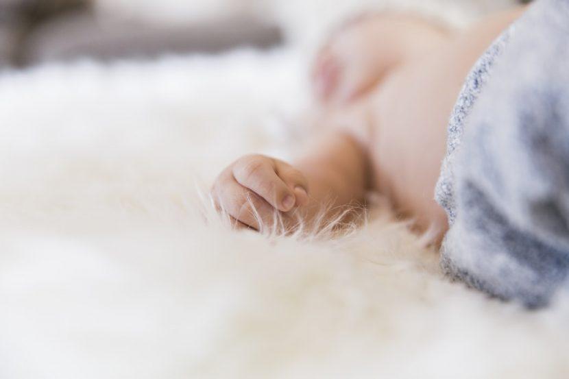 Koraszülött gyerekruha, ici-pici baba fekszik az ágyon, kép.
