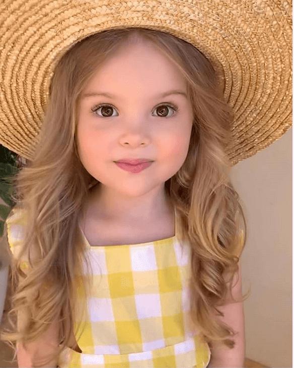Nyaralás babával, szalma kalapos kislány, sárga kockás nyári ruhában, kép.