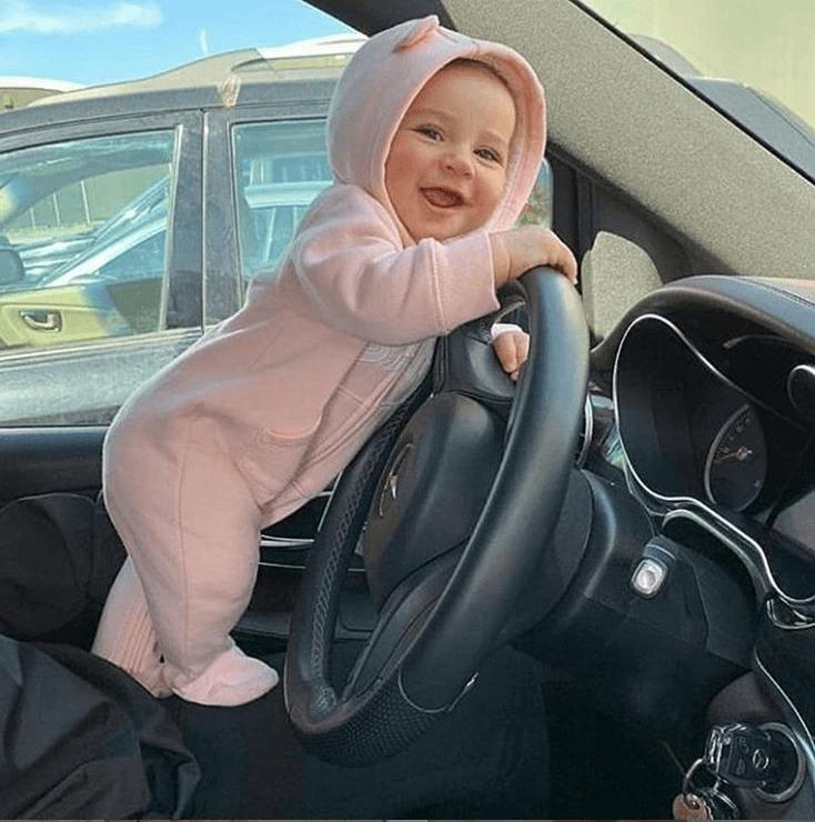Utazás babával, kisbaba fogja a kormányt az autóban és mosolyog, kép.