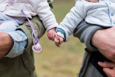Hordozókendő, kenguru, két csecsemőt ölben sétáltatnak a szabadban, kép.