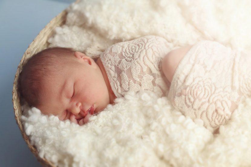 Baba öltöztetése, kosárban, fehér szőrme közt alvó kisbaba, kép.