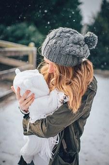 Baba öltöztetése télen, melegen felöltöztetett kisbaba az édesanyja karjaiban, kép.
