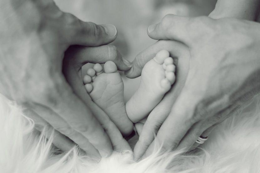 szülés utáni időszak, újszülött kis lábai az anyuka kezében, kép.