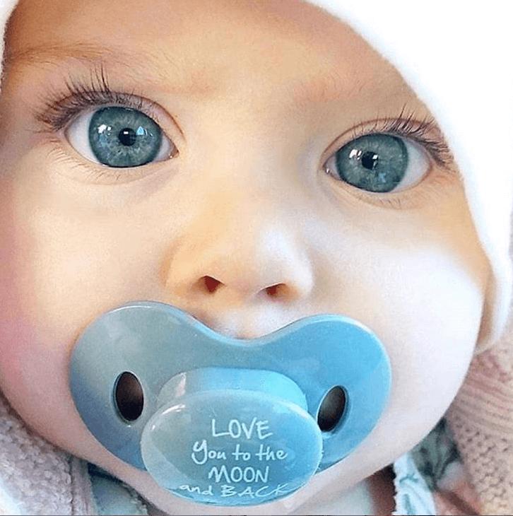 kisbaba születik, kék szemű kisbaba arc, cumival a szájában, kép.