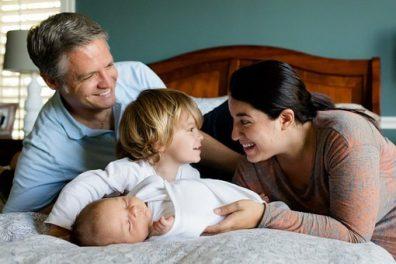 szülés utáni fáradtság, anyuka, apuka, kislány és újszülött kisbaba fekszik az ágyon, kép.