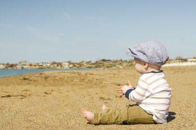 Baba öltöztetése nyáron, tengerparti homokban, melegben, kisgyermek ül kalapban, termékkép.