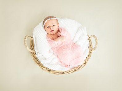 Babamasszázs, csecsemő fekszik egy fonott kosárban, rózsaszín takaróban, kép.