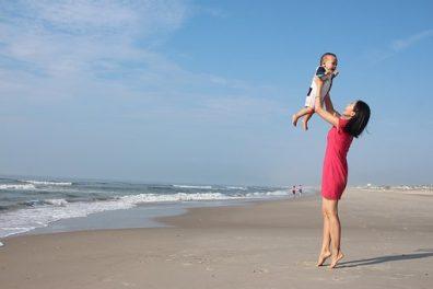 Szülés utáni érzelmek, anyuka magasba emeli a kisbabáját a tengerparton, kép.