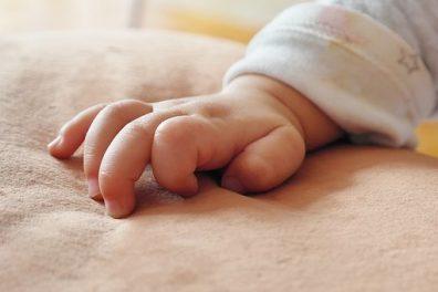 Újszülött vizsgálatok, pici baba keze látszik a takarón, kép.