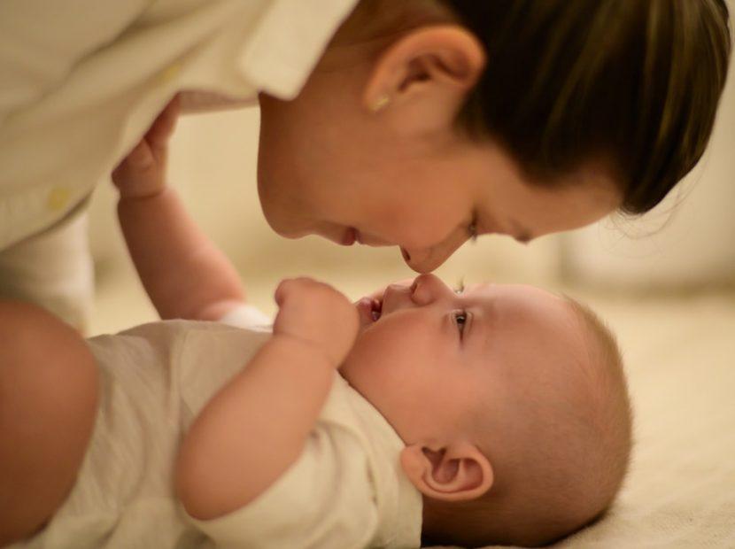 Szülés utáni élet, anyuka a kisbabája fölé hajol, kép.