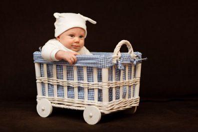milyen nevet adjak a fiamnak, kisbaba ül egy fonott kis kocsiban, kép.