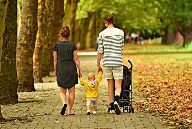 Család lettünk, anyuka és apuka sétál, középen a kisgyermekük, mindkettőjük kezét fogja és sétálnak a parkban, sárga falevelek közt, kép.
