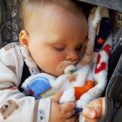Csecsemőgondozás, csecsemő békésen alszik a képen a takaróján, cumival a szájában, kép.