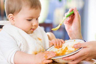 Milyen bébiszittert válasszak, egy bébiszitter nő etet kanállal egy kislányt, kép.