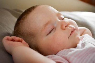 baba alvási szokásai, kisbaba alszik felhajtott karokkal, kép.