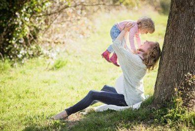 Egyedülálló szülő, anyuka felemeli a magasba a kisgyermekét egy parkban a fa alatt ülve, kép.