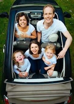 Több gyermekes szülők, apuka, anyuka és három gyermek ül egy autóban, a kép felül nézetből készült, kép.
